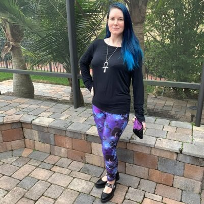 Courtney is wearing a minimalist Prana Synergy Top, Hell Bunny Orpheus Leggings, Tuk Eyelet Strap Pointed Creepers, Avelina De Moray Mahafsoun Wallet and an ankh necklace
